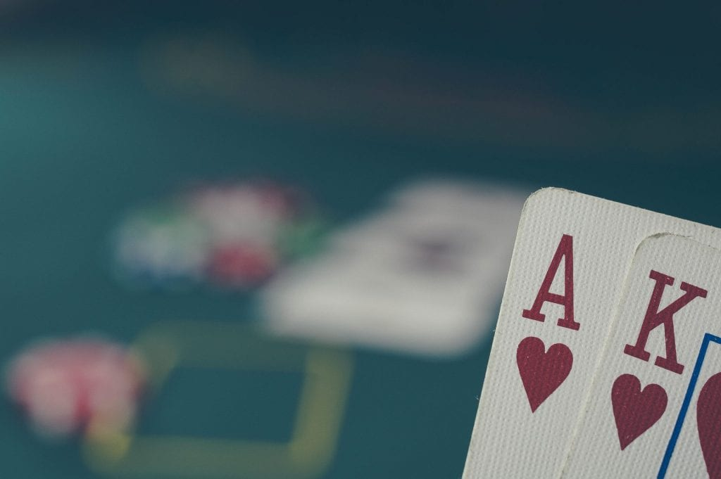 closeup of Ace and King of hearts cards with blackjack table in the background   how to negotiate with suppliers